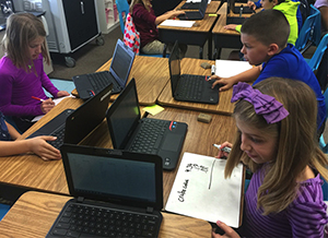 Three students collaborate using laptop computers