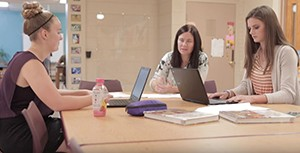 Two students and a teacher sit at a table to collaborate.
